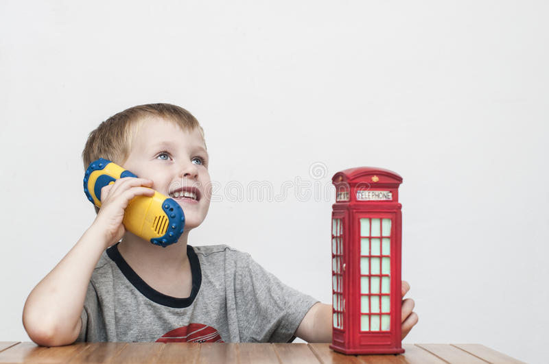 Boy talking on the phone and red telephone booth stock photos