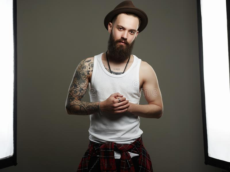 Boy with tattoo. Male model in Photostudio. Tattooed handsome Bearded Man in Hat. Brutal hipster boy with tattoo. Male model in Photostudio stock photography