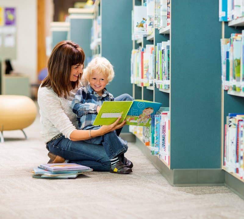 Boy And Teacher Reading Book By Bookshelf. Full length of smiling boy and teacher reading book by bookshelf in library stock photo