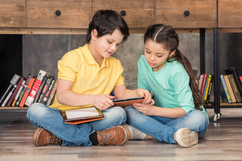 Boy teaching focused girl how to use digital tablets stock photos