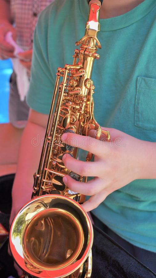Young man plays mini saxophone with bare hands stock photo
