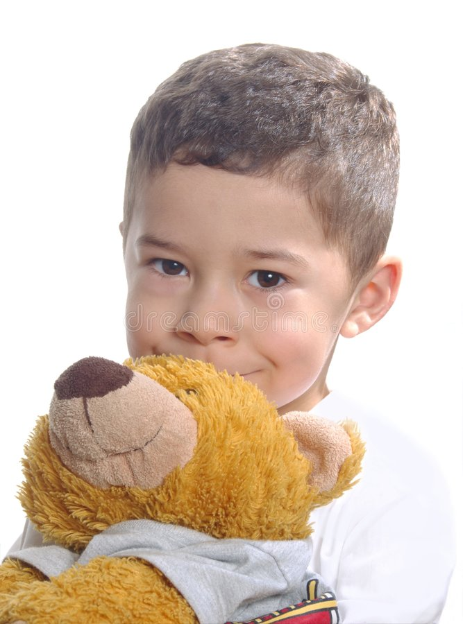 Boy With Teddy Bear. A young boy smiling behind his teddy bear stock photography