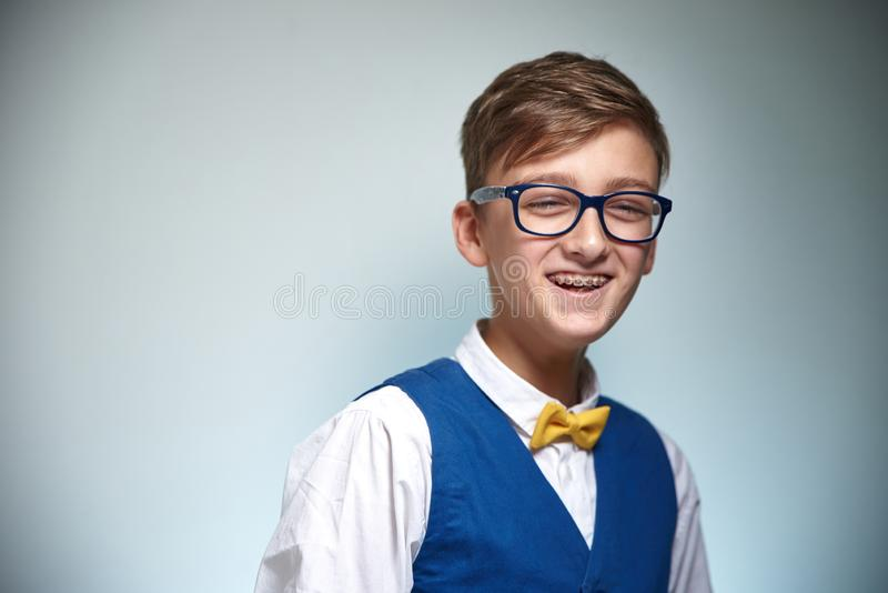 Boy teenager with braces in glasses. Wearing a shirt with a bow tie. royalty free stock photography