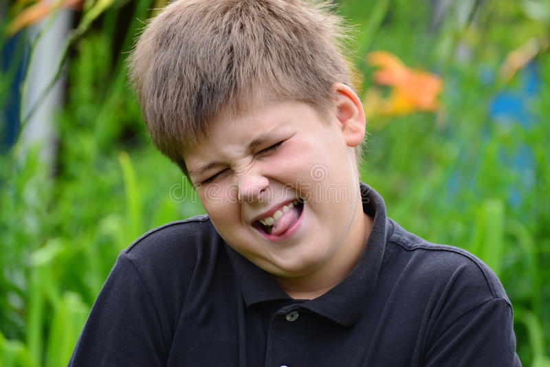Boy teenager face contorts in nature royalty free stock image
