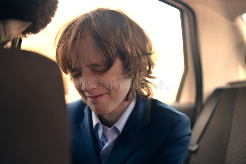 A boy is a teenager with a long hair in a classic suit in the car. stock photos