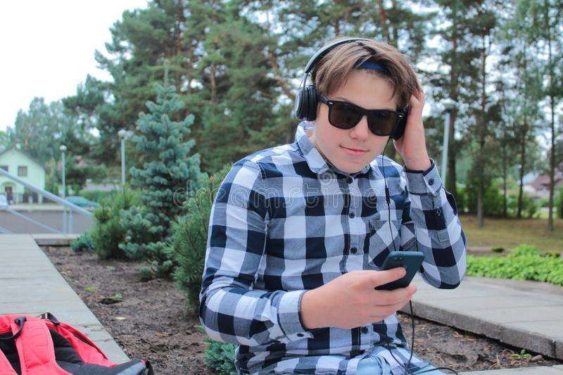 Boy teenager schoolboy or student in a shirt, smiles in glasses, listens to music on the phone. Red backpack, school background royalty free stock image