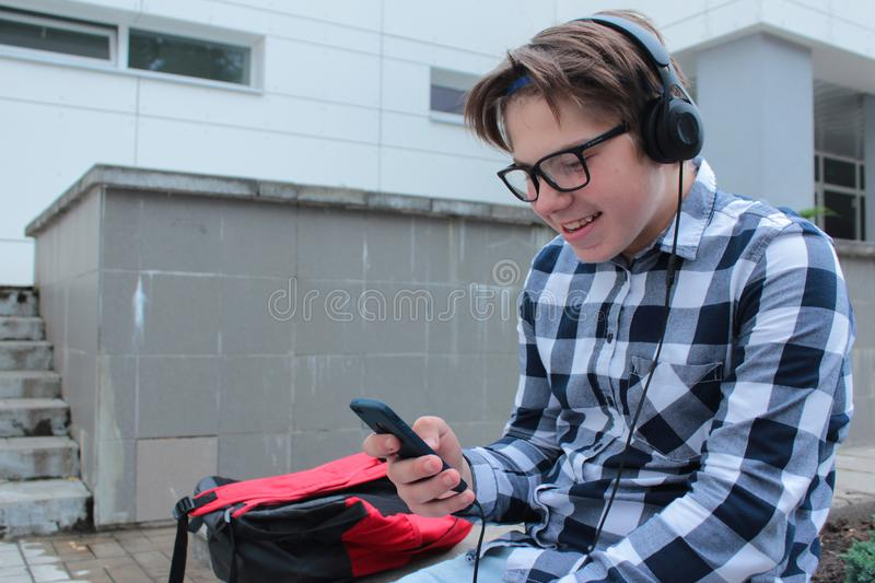 Boy teenager schoolboy or student in a shirt, smiles in glasses, listens to music on the phone. Red backpack, school background royalty free stock photos