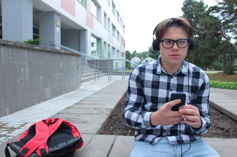 Boy teenager schoolboy or student in a shirt, smiles in glasses, listens to music on the phone. Red backpack, school background royalty free stock photography