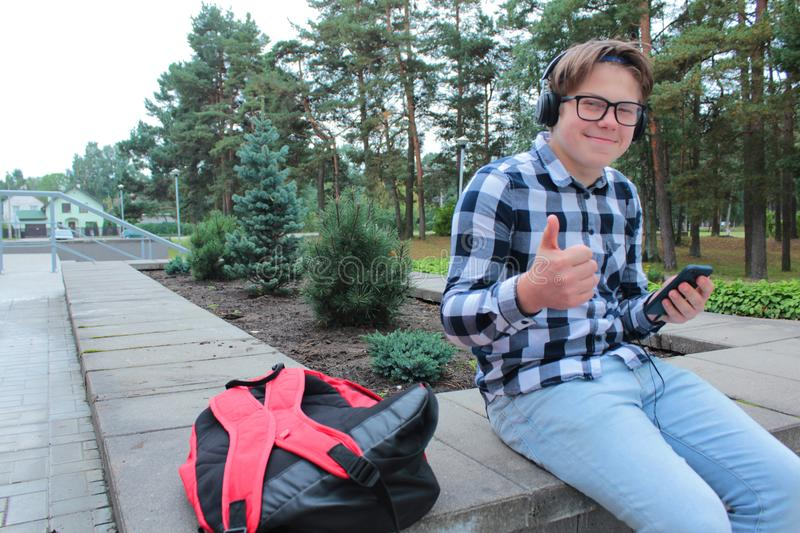 Boy teenager schoolboy or student in a shirt, smiles in glasses, listens to music on the phone. Red backpack, school background stock photography