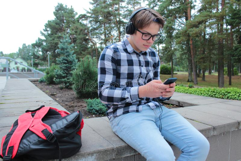 Boy teenager schoolboy or student in a shirt, smiles in glasses, listens to music on the phone. Red backpack, school background royalty free stock images