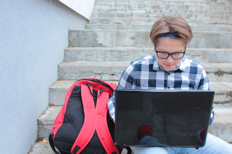 Boy teenager schoolboy or student is sitting on the stairs, working in the computer, wearing glasses, in a shirt, smiling, red b. Ackpack royalty free stock photo