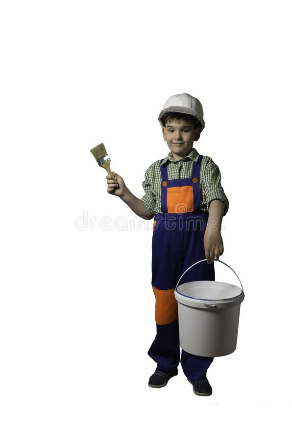 Boy, teenager with tools for repair and construction, in overalls and helmet, isolated. stock photo