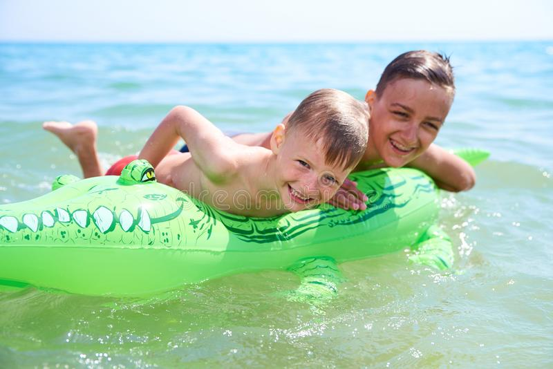 BOY OF TEENAGERS IN WATER GOGGLES SWIMS ON THE INFLATABLE TOY CROCODILE. BOY OF TEENAGERS AND HIS LITTLE BROTHER IN WATER GOGGLES SWIMS ON THE INFLATABLE TOY stock photos