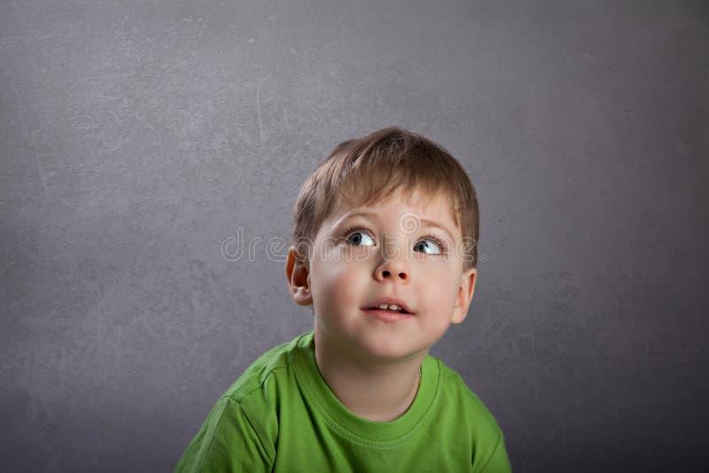 Boy thinking. On grey grunge background royalty free stock photos