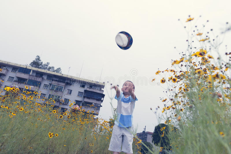 Boy throw hat. Chinese boy throw hat air hardly in garden stock images