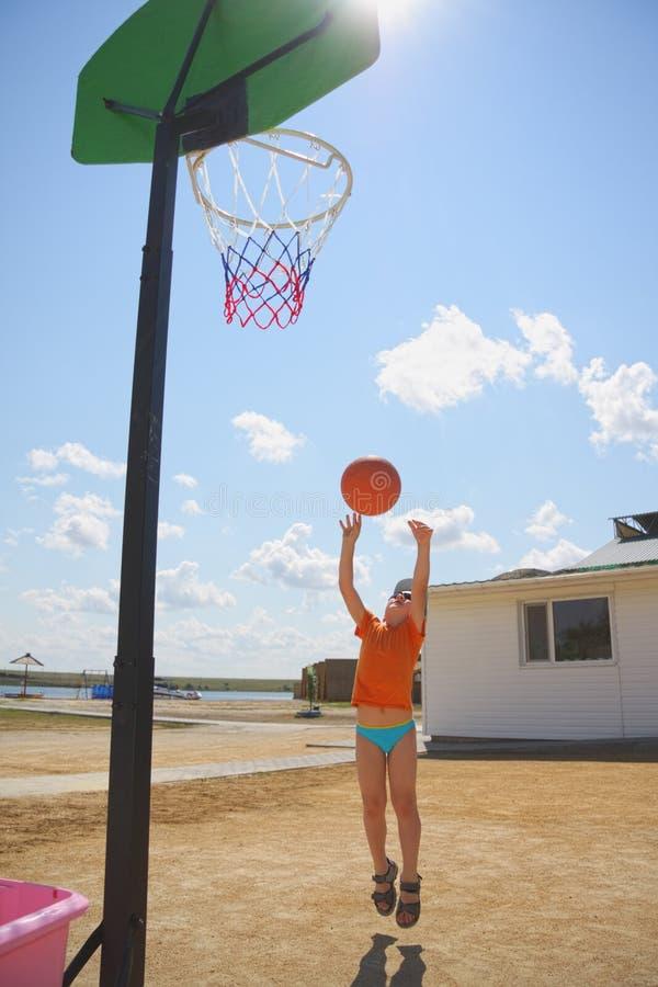 Boy throwing ball to basket royalty free stock photo