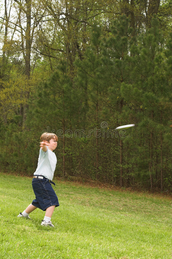 Boy throwing frisbee royalty free stock photo