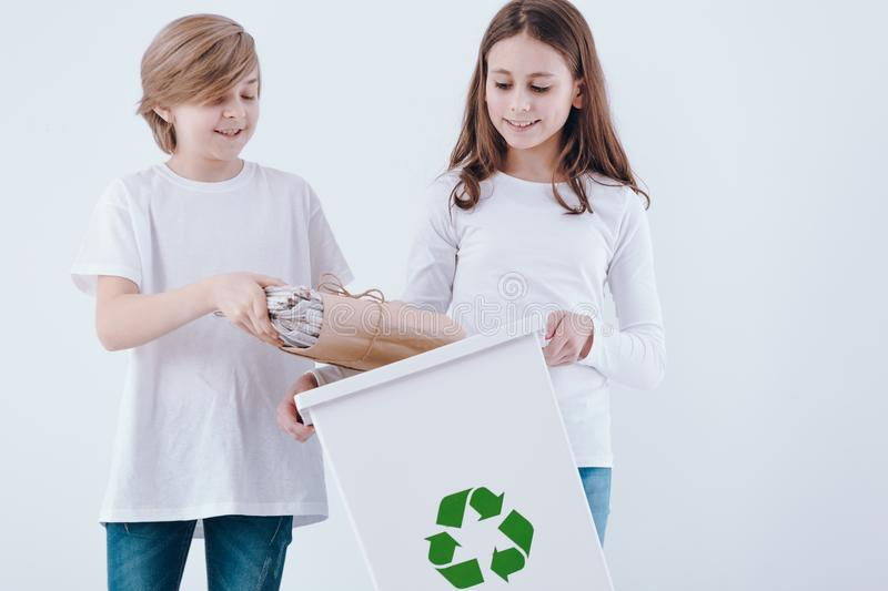 Boy throwing paper into bin stock image