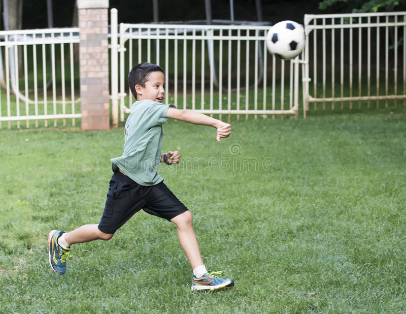 Boy throwing a soccer boy. A ten year-old Amerasian boy is running is short green grass. He is throwing a soccer ball forward with vigor with his right arm royalty free stock photo