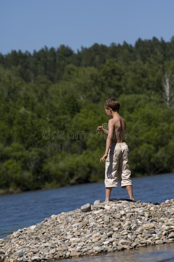 Boy Throwing Stone In Lake Royalty Free Stock Photo