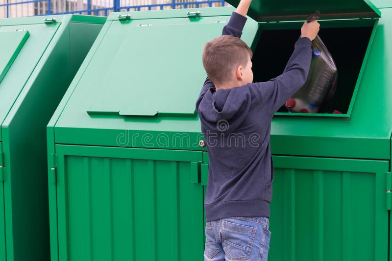 Boy throws black bag with waste in trash tank stock image