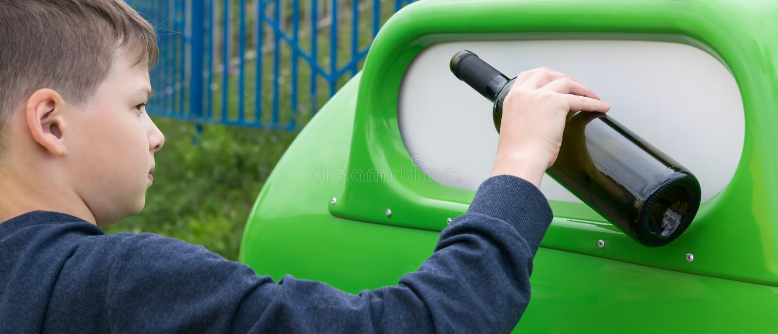 A boy throws a bottle from under the wine into the trash tank, rear view royalty free stock photography