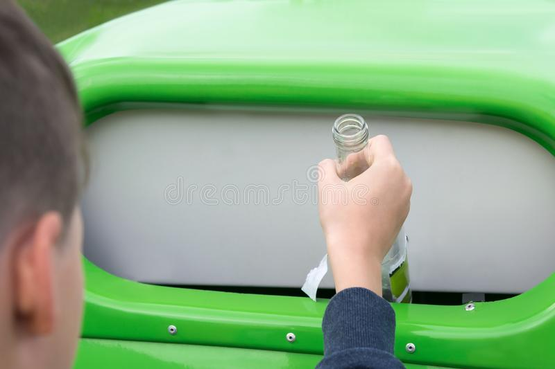 A boy throws an empty glass bottle into a special container for glass, close-up stock photo