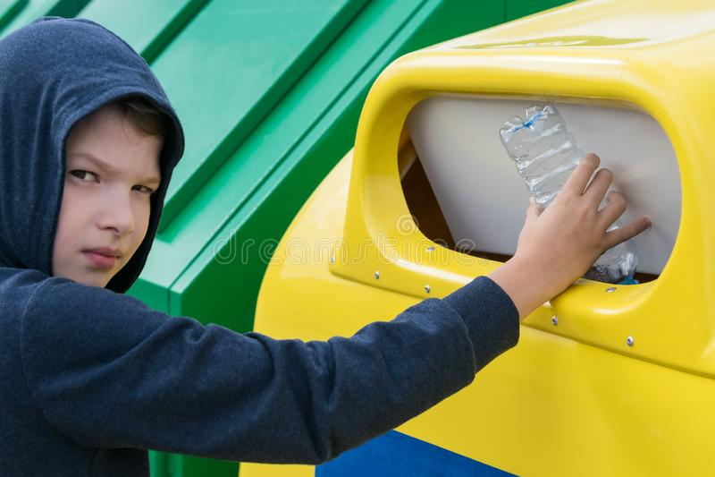 Boy throws an empty plastic bottle into a container for collecting separate garbage royalty free stock photos