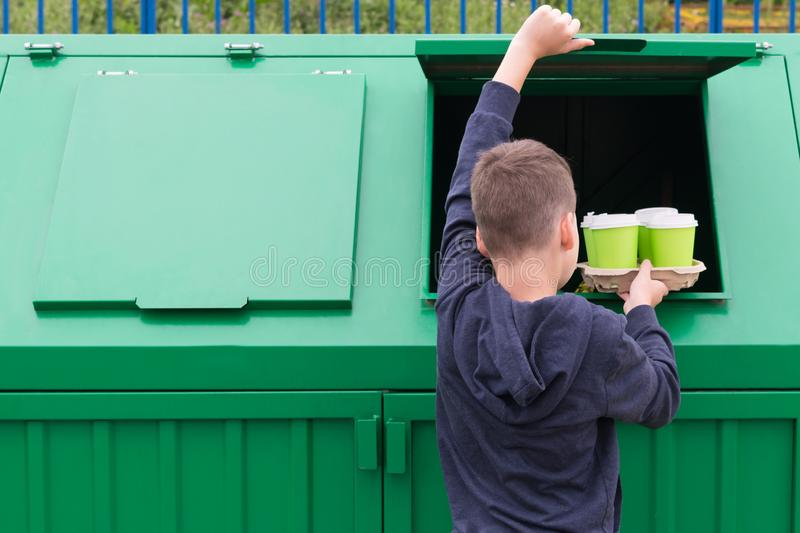 The boy throws out four glasses from under the drinks in the trash can, rear view, on the left there is a place for your stock photo