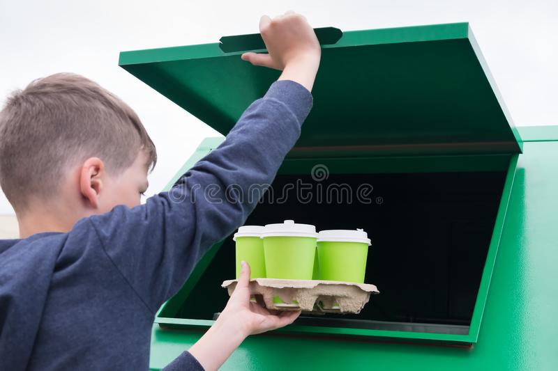 Boy throws a paper stand with empty cups in the trash tank stock images
