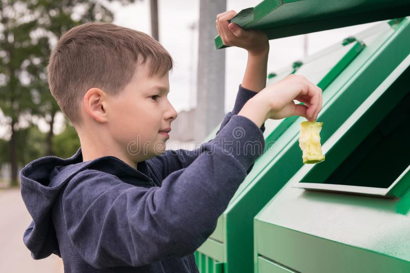 Boy throws a piece of apple into the trash tank, close-up stock photo