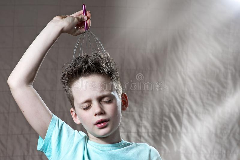 Boy tickles his head with a scratcher and covered his eyes with pleasure stock images