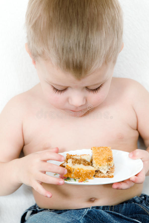 The boy to school age with a pie. In hands royalty free stock images