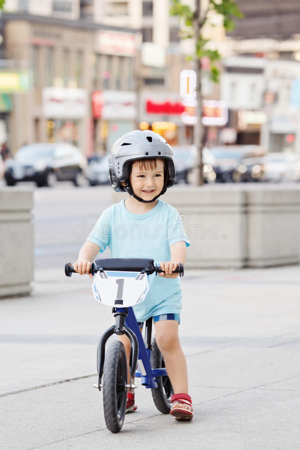 Boy toddler riding a balance bike bicycle in helmet on the road. Portrait of smiling little boy toddler riding a balance bike bicycle in helmet on the road royalty free stock photos