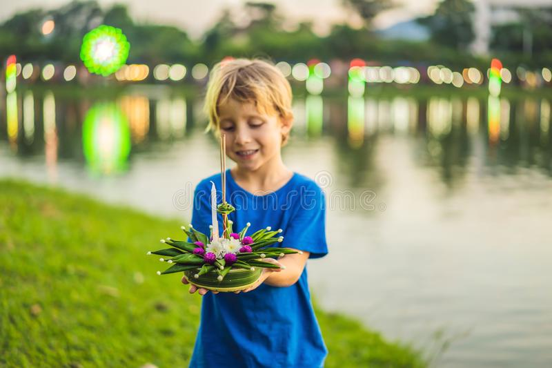 Boy tourist holds the Loy Krathong in her hands and is about to launch it into the water. Loy Krathong festival, People. Buy flowers and candle to light and stock image