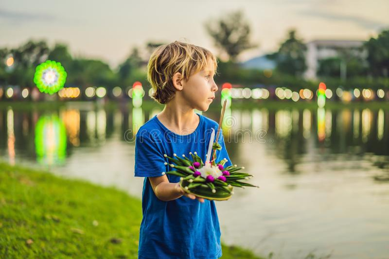 Boy tourist holds the Loy Krathong in her hands and is about to launch it into the water. Loy Krathong festival, People. Buy flowers and candle to light and stock photography