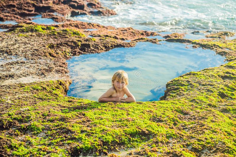Boy tourist on Pantai Tegal Wangi Beach sitting in a bath of sea water, Bali Island, Indonesia. Bali Travel Concept. Traveling with children concept. Kids stock photo