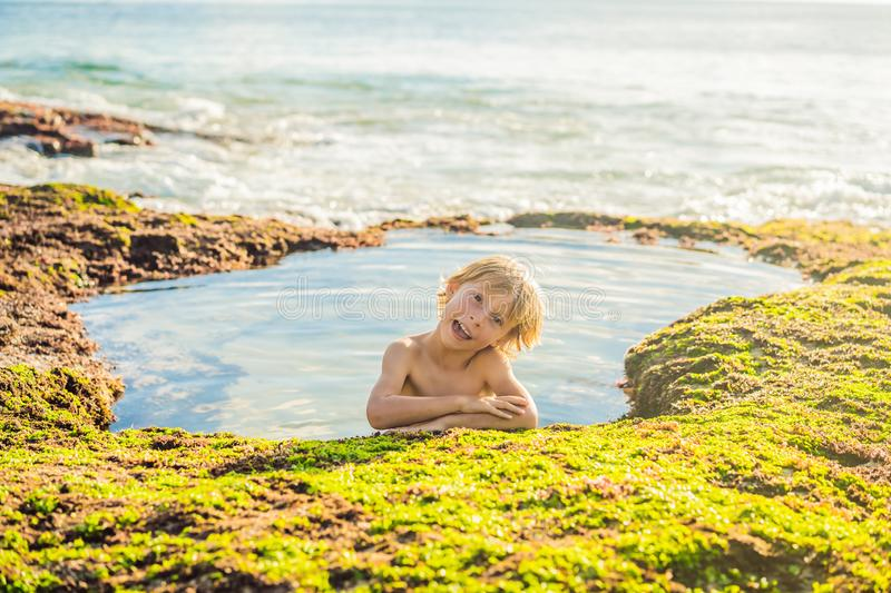 Boy tourist on Pantai Tegal Wangi Beach sitting in a bath of sea water, Bali Island, Indonesia. Bali Travel Concept. Traveling with children concept. Kids stock photos