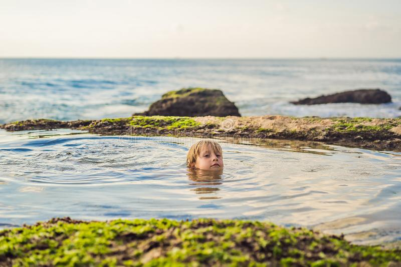 Boy tourist on Pantai Tegal Wangi Beach sitting in a bath of sea water, Bali Island, Indonesia. Bali Travel Concept. Traveling with children concept. Kids royalty free stock images
