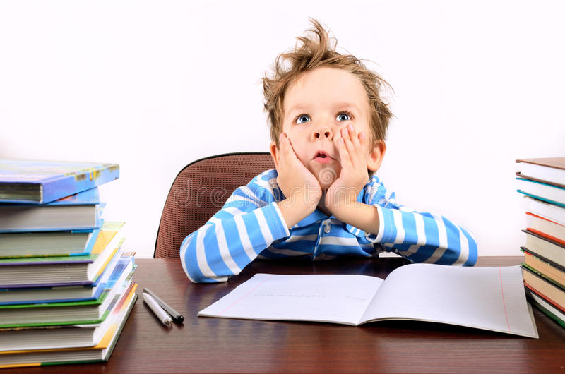 Boy with tousled hair sitting at a desk. Boy is 5 years. horisontal royalty free stock image