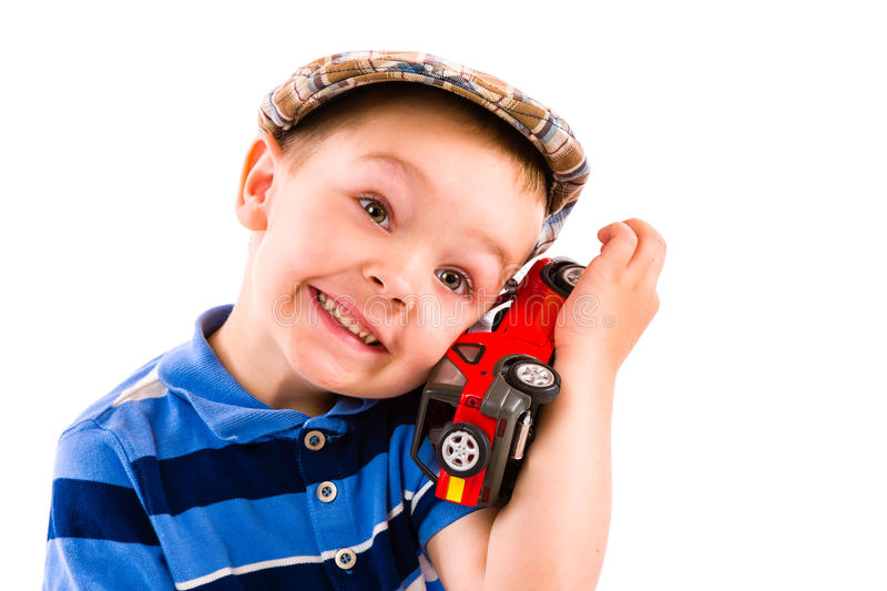 Boy and toy car. Little boy plays with red toy car, white background stock image