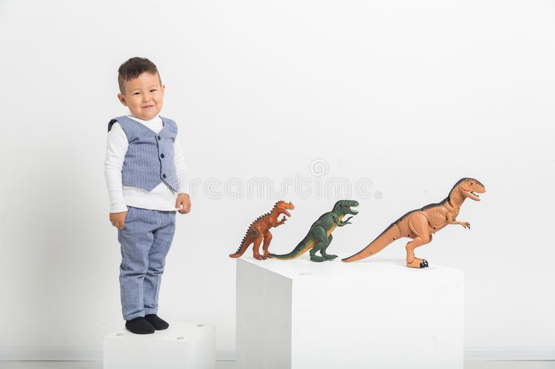 Boy with toy dinosaurs on white background, baby Asian stock image
