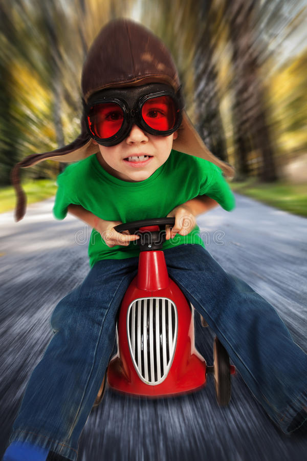 Boy on toy racing car. Boy in retro racing hat and goggles driving on toy car at speed with blurred background royalty free stock photography
