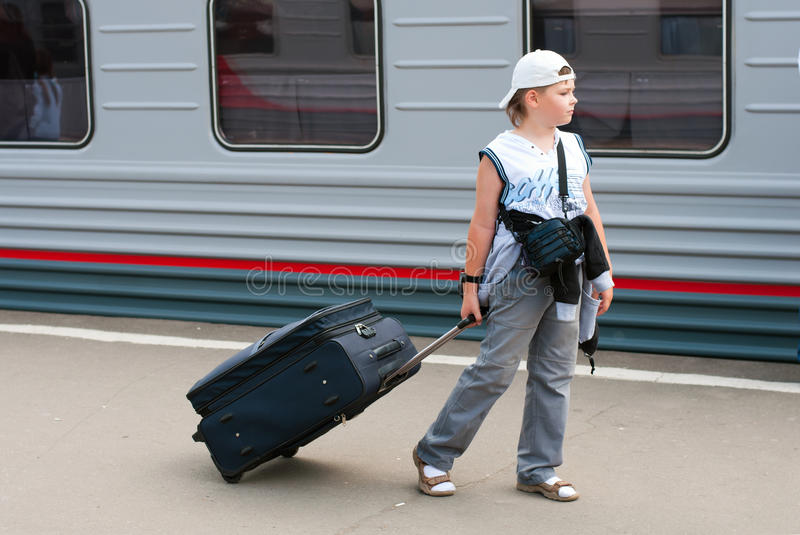 Boy with travel bag near train royalty free stock photos