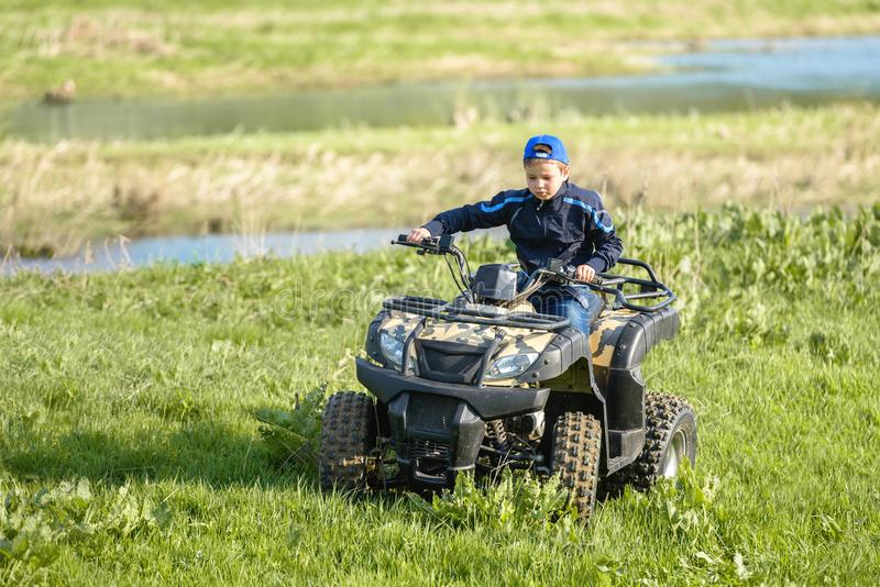 The boy is traveling on an ATV stock image