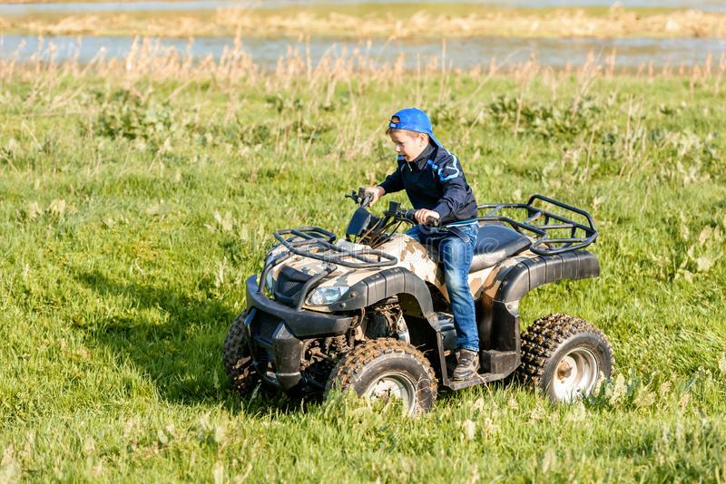 The boy is traveling on an ATV royalty free stock photos