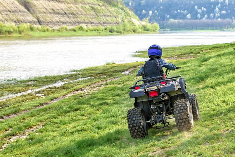 The boy is traveling on an ATV stock photo