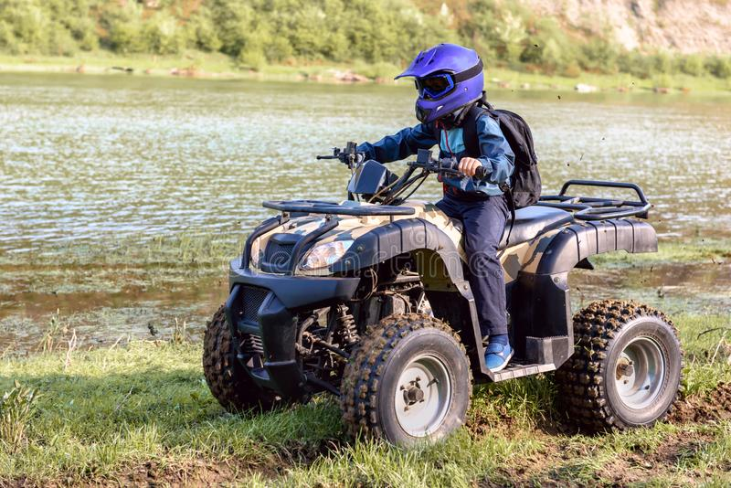 The boy is traveling on an ATV royalty free stock images