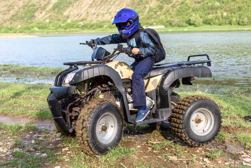The boy is traveling on an ATV stock photography
