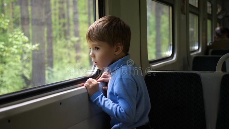 The boy is traveling by train and looks out the window, watching the moving objects outside the window. Travelling with stock photography